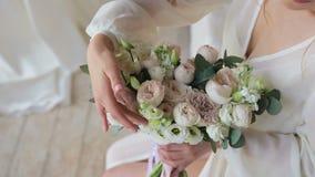 Morgonnygifta personer En ung brud i en vit negligé undersöker och trycker på bröllopbukettsammanträdet på sängen arkivfilmer