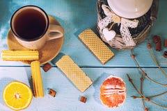 Morgonplatsen med kopp te eller kaffe, holländsk kakastroopwafel, delftfajans slösar souvenir, på blåtttabellen royaltyfri bild