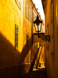 MorgonPrague plats Solbelysta och långa skuggor på väggen med gasgatalampan, Thunovska gata, Lesser Town, Prague Royaltyfri Foto