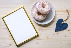 Morgonsammansättning med donuts på en trätabell Guld- ram för presentationen av arbeten eller text fotografering för bildbyråer