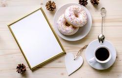 Morgonsammansättning med kaffe och donuts på en trätabell Guld- ram för presentationen av arbeten eller text royaltyfri bild