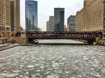 Morgonsikt av djupfrysta Chicago River och omgeende cityscape under tungt snöfall royaltyfria bilder