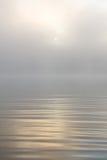 Morgonsol till och med dimma på sjön Arkivbilder