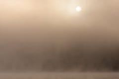 Morgonsol till och med dimma på sjön Arkivfoton