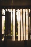 Morgonsolen som skiner till och med ett fönster och träslutare på myggnät, och gardiner i en djungel inkvarterar i Sri Lanka arkivfoton
