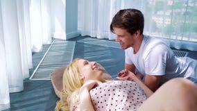 Morgonsolsken på lyckliga unga par i hem- kläder som ligger på golv i tomt rum stock video