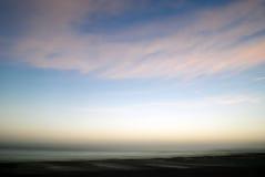 Morgonsoluppgång över kropp av vatten med molnig himmel Fotografering för Bildbyråer