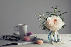 Morgonstilleben med tappning steg i en vas, ett kaffe och macarons på en ljus tabell Härlig och hemtrevlig frukost Royaltyfria Bilder