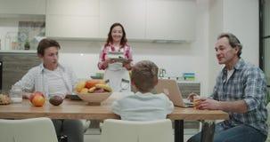 Morgontid i en attraktiv familj för modernt kök som tillsammans tar mamman för frukost som förbereder tabellen med den smaskiga m arkivfilmer
