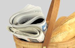 Morgontidningar och nytt bröd i korg Arkivbilder