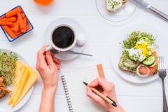 Morgonvanor av lyckat folk Dagplanläggning och sunt äta Kvinnadrinkkaffe och handstil i anteckningsboken på som tjänas som för royaltyfri fotografi