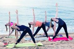 Morgonyoga på stranden, grupp av unga kvinnlig royaltyfria bilder