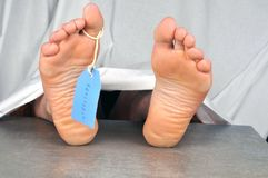 Corpse with a tag on the toe. Morgue concept with a cadaver carrying a tag on the toe stock images