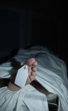 Morgue Scene. Dark atmospheric photo of body covered with a sheet in a morgue, feet toward camera with blank tag on the big toe. Foot clearly shows flaking skin Royalty Free Stock Photography