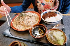 Yummy japanese cusine, a female hand trying to use chopsticks, cold soba noodles and curry rice placed on table. Mori/Zaru Soba, Yummy japanese cusine, a female royalty free stock photo