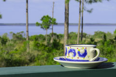Moring Coffee and View. A coffee cup and saucer rests on the porch railing for a morning view of St. Andrews East Bay in Panama City, FL Royalty Free Stock Image