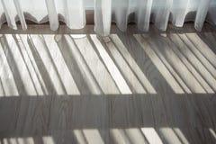 Moring ilumina a proteção do branco e cria um teste padrão da sombra no assoalho Fotos de Stock