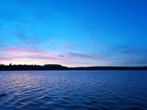 Moring sikt förutom den fridsamma sjön med blåa färger Royaltyfri Bild