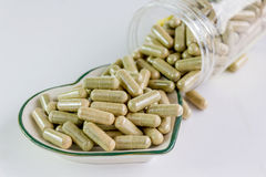Moringa capsules on small heart pattern bowl Stock Images