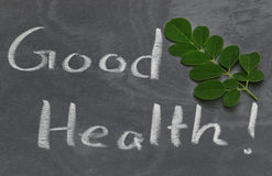 Moringa leaves with Good Health written in a slate. By whtie chalk stock image