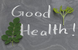 Moringa leaves with Good Health written in a slate Stock Photos