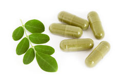 Moringa oleifera capsule. With green fresh leaves on white background Royalty Free Stock Photography