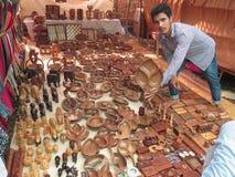 Morjim, India, Listopad 23, 2013 W rynku, Indiański mężczyzna pokazuje kupować drewnianego talerza i oferuje obrazy stock