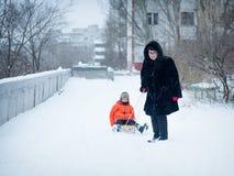 Mormodern drar släden med behandla som ett barn Vintern går nära huset royaltyfri foto