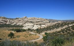 Mormon Rocks Panorama. Mormon rocks geological formations and a meadow beneath blue sky, California Stock Photography