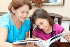 Mormor och flicka som läser en bok Royaltyfri Foto