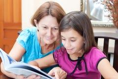 Mormor och flicka som läser en bok Royaltyfria Foton
