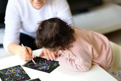 Mormor- och sondotterteckning samman med pinnen på magiskt skrapamålningpapper hemma eller i grupp royaltyfri bild