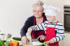 Mormor och sonson som tillsammans lagar mat royaltyfria foton