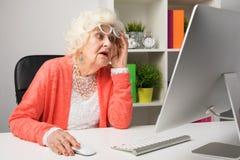 Mormor som arbetar på kontoret och ser datoren i misstro royaltyfri foto