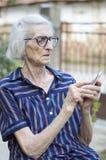 Mormor som försöker att använda den moderna smartphonen utomhus fotografering för bildbyråer