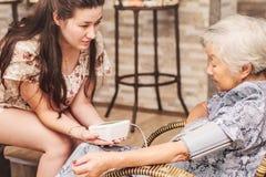 Mormor som hemma gör en kontroll-upp på hälsan royaltyfri foto