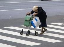 Mormor som korsar gatan Arkivfoto