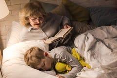Mormor som läser till Little Boy royaltyfri bild