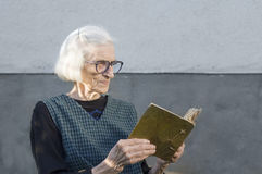 Mormor som ser familjfotoalbumet Arkivbilder