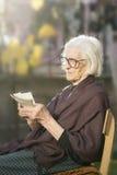 Mormor som ser några mycket gamla foto arkivfoto