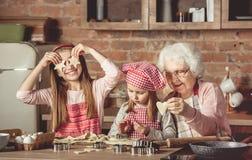 Mormorundervisningsondöttrar som bakar kakor Royaltyfri Fotografi