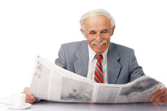 In The Morning. Portrait of an elder happy man reading a newspaper with a cup near him Royalty Free Stock Image