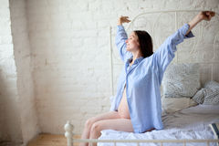 Morning. Young pregnant woman sitting on the bed in the morning and stretching herself Royalty Free Stock Photo