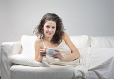 Morning. Smiling beautiful woman lying on a sofa and holding a cup of tea Stock Photos