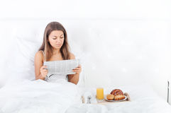 Morning. Bedtime collection: young woman reading a newspaper in bed Royalty Free Stock Photos
