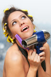 The morning. Portrait of girl in hair rollers with hair-dryer and comb (shallow DOF Stock Images
