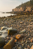 Morning on Acadia Boulder Beach. Rounded stones on Boulder Beach looking toward the Otter Cliffs at sunrise in Acadia National Park, Maine Stock Photos