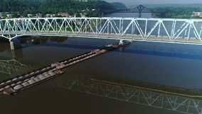 Morning aerial view of barge on Ohio river traveling under bridge. A morning aerial establishing shot of a coal barge traveling under a bridge on the Ohio River stock video