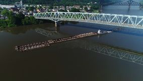 Morning aerial view of barge on Ohio river traveling under bridge. A morning aerial establishing shot of a coal barge traveling under a bridge on the Ohio River stock video footage
