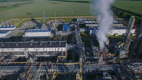 Morning aerial flying panorama over chemical plant produces gasoline and mineral fertilisers. Sunshine summer fields and